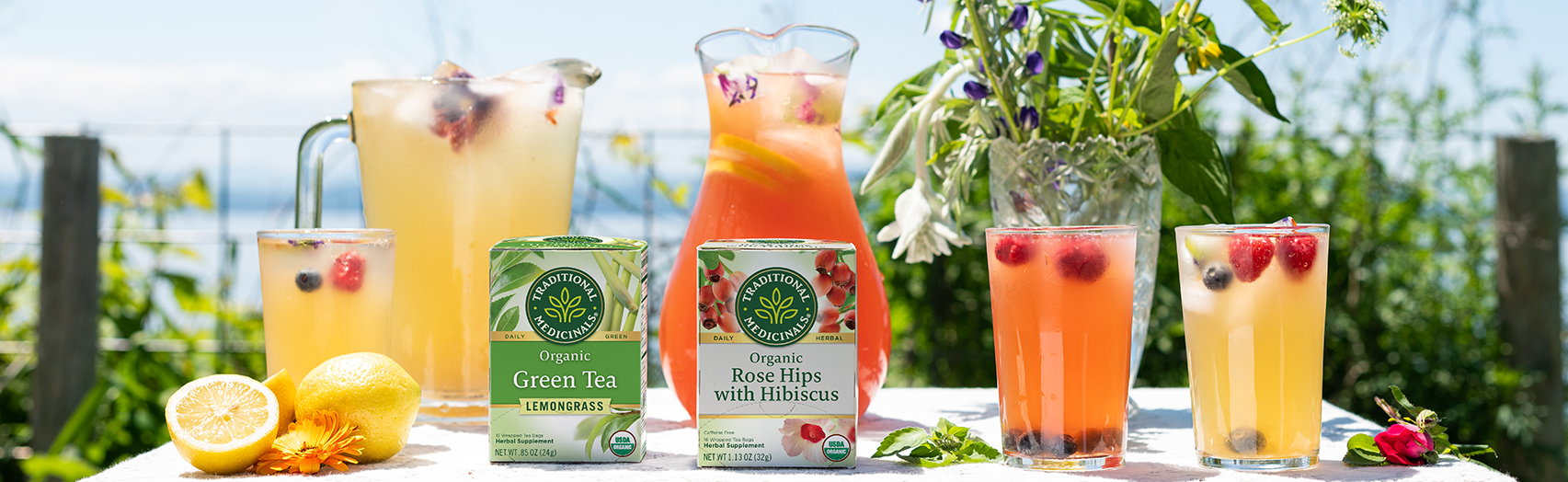 Herbal lemonade in pitchers and glasses with Green Tea Lemongrass and Rose Hips with Hibiscus cartons on table