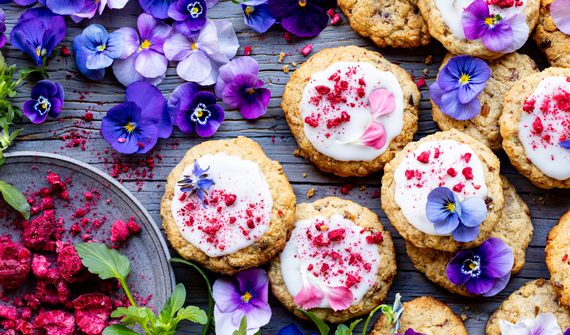 Beautiful array of herbal lactation cookies decorated with pink and purple edible flowers